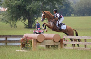 Horse and rider jumping cross country jump during eventing competition